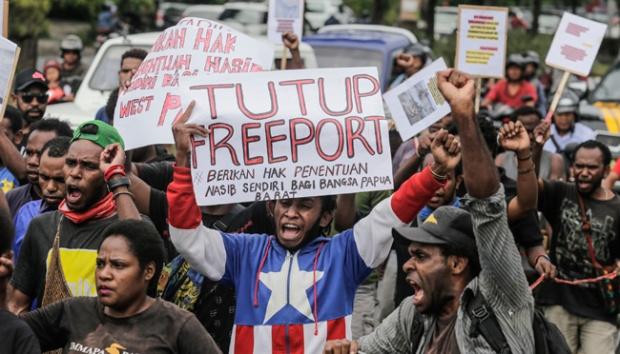 Sejumlah Mahasiswa asal Papua membawa poster dan meneriakan yel-yel saat aksi menuntut ditutupnya PT Freeport Indonesia di depan kantor Konsulat Jenderal Amerika Serikat di Denpasar, Bali, 20 Maret 2017. Sejumlah aktivis di beberapa daerah di Indonesia menggelar aksi untuk menuntut ditutupnya Freeport. Foto: Johannes P. Christo