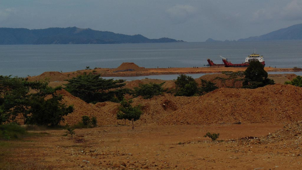 Tanah merah berisi batu atau dikenal dengan nikel ore menumpuk di dekat pesisir pantai di Kecamatan Pomalaa, Kabupaten Kolaka, Sulawesi Tenggara, Jumat (3/11). Nelayan di sekitar tambang mengeluhkan air laut yang kemerahan beberapa tahun terakhir. Mereka terpaksa melaut lebih jauh untuk mencari ikan. Foto: KOMPAS/ABDULLAH FIKRI ASHRI